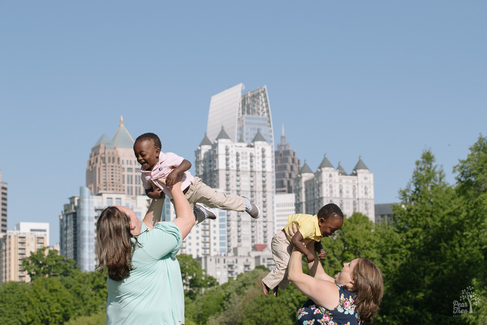 Two moms tossing their toddler twin boys up into the Atlanta skyline