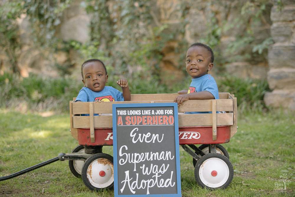 Twin African-American toddler boys sitting in wagon with Superman adoption sign