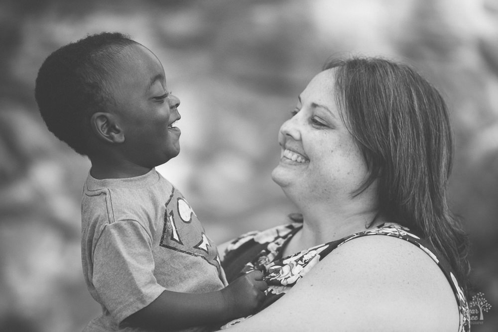 Caucasian mom holding and smiling at her adopted African-American son