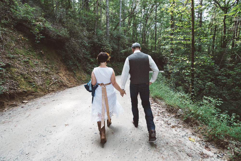Bride + groom holding hands while walking along mountain road
