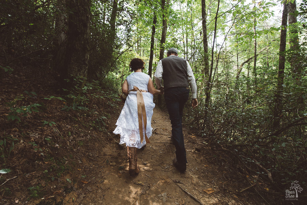 Bride + groom holding hands while walking through mountain forest