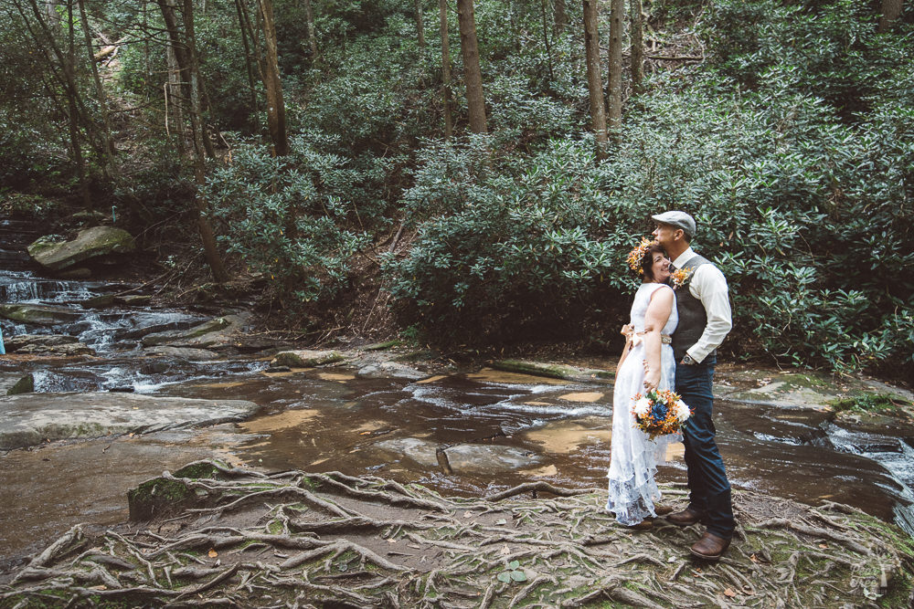 Bride leading into groom next to mountain stream
