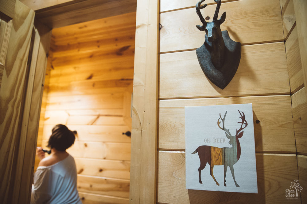 Bride getting ready in mountain cabin bathroom with Oh Deer sign