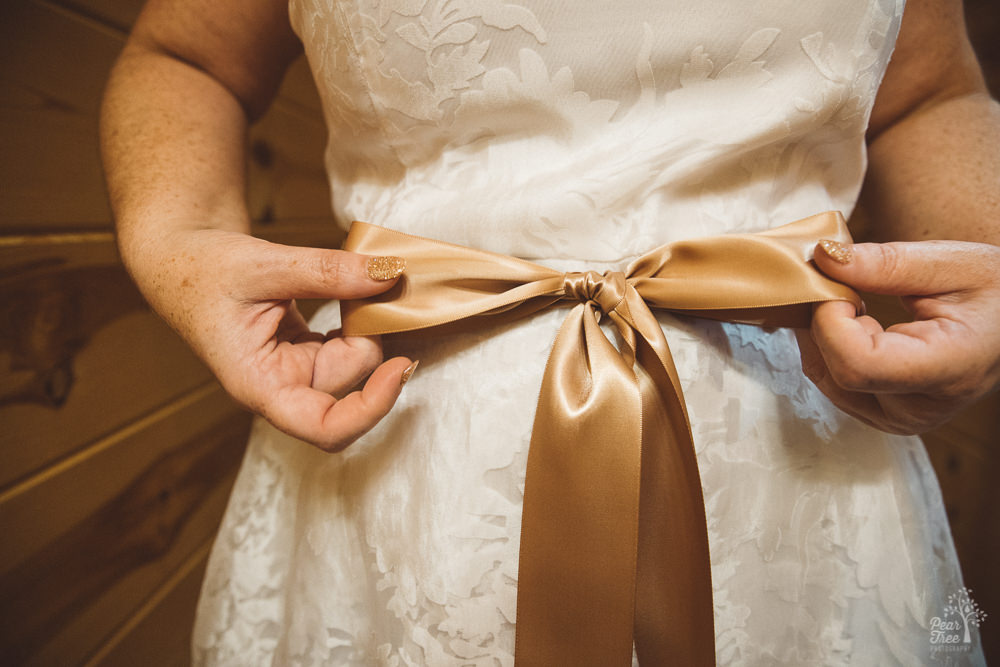 Bride's hands tying bow in ribbon around her waist