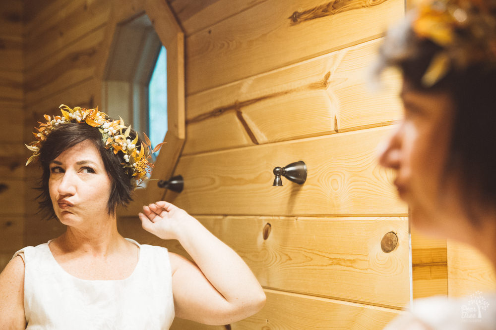 Bride inspecting her floral headdress in cabin bathroom mirror