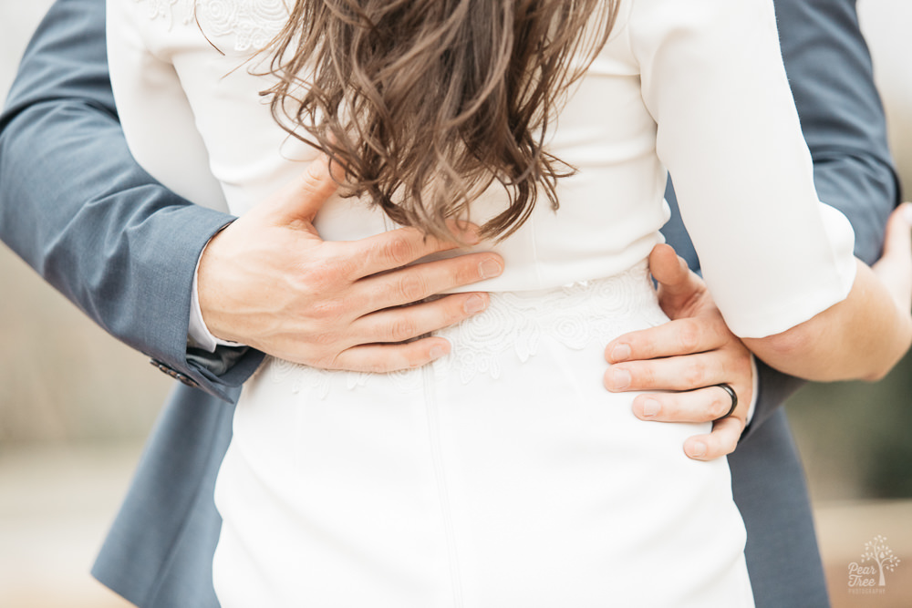 A man's hands wrapped around his fiance's back underneath her long, curly hair