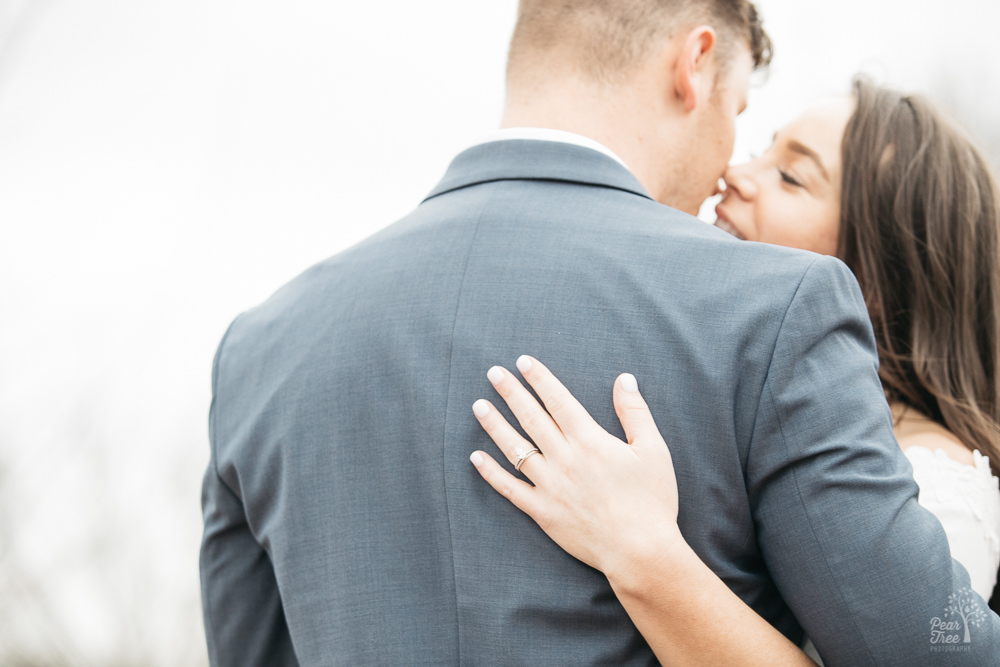 A romantic couple embracing and almost kissing. Her engagement ring is clearly seen on her hand wrapped around his back