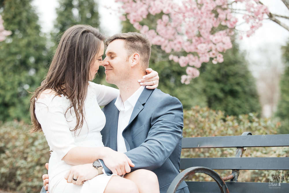 A gorgeous engaged couple sitting on a park bench almost kissing