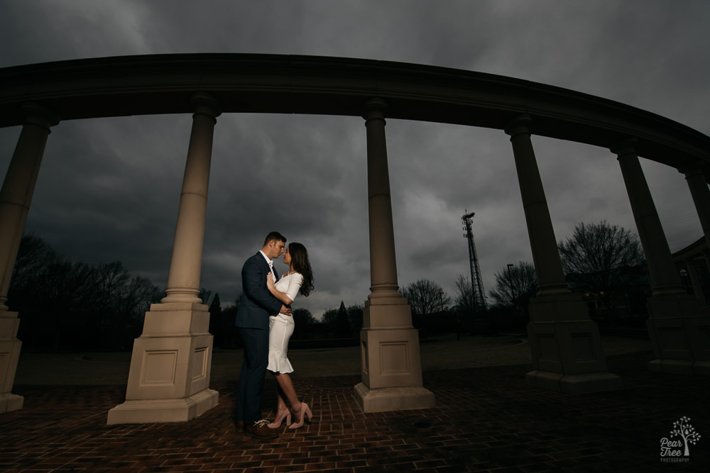 Engaged couple embracing under archway in Newnan park with dramatic stormy skies in background