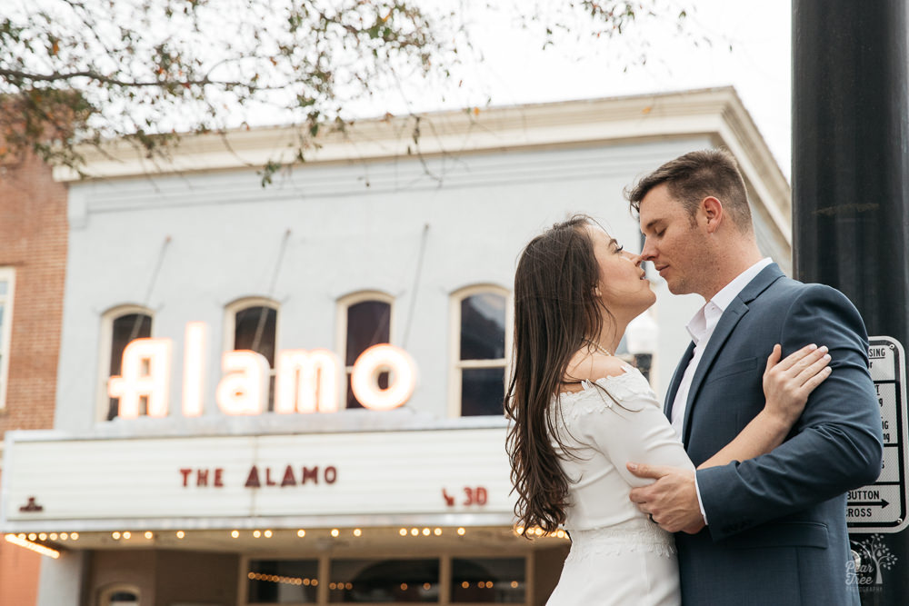 Couple almost kissing in front of Newnan Alamo Theatre