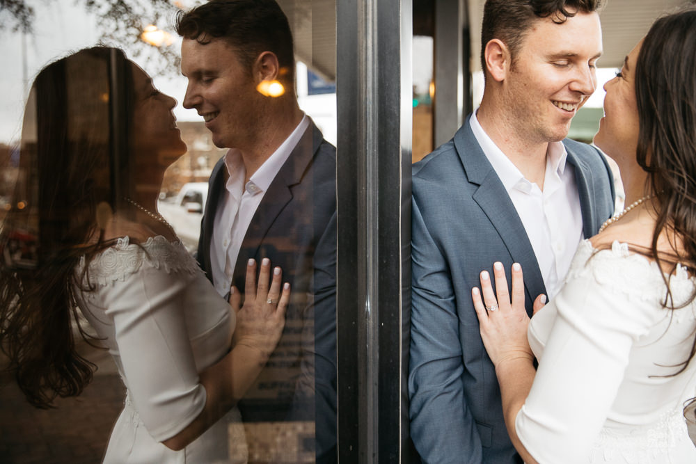 Couple smiling and holding each other while reflected in shop windows