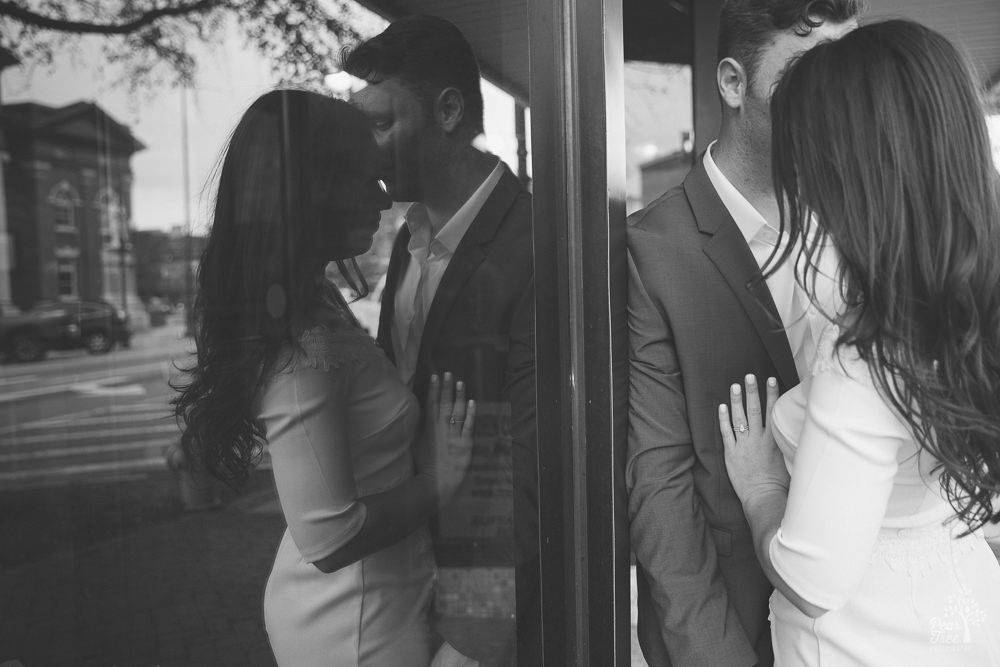 Couple nuzzling close while reflected in Newnan storefront windows