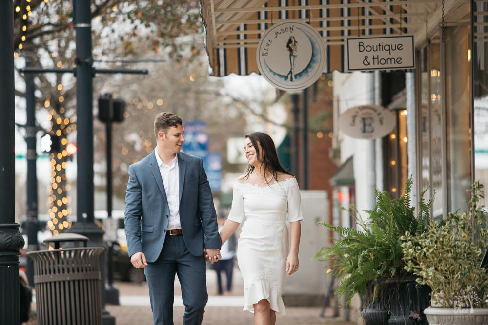 Couple smiling and holding hands while walking through Newnan Square