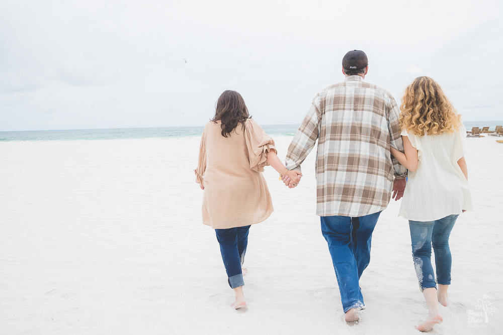 Family holding hands while walking on beach