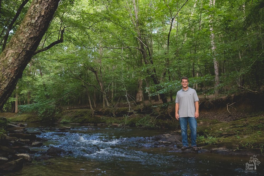 High school senior boy standing in the middle of a creek