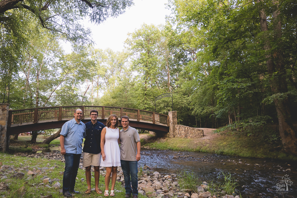 Two parents standing with their teenage boys in front of a bridge and creek.