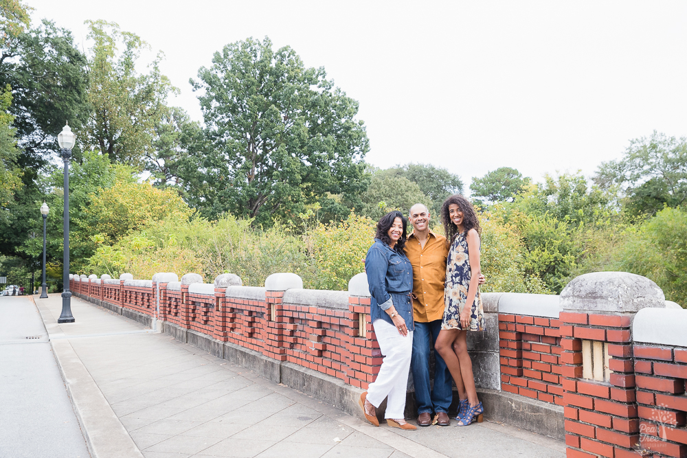 Family of three standing on old brick bridge in Piedmont Park and smiling