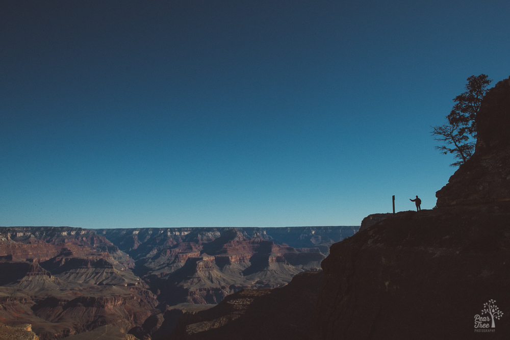 Man waving in silhouette on the Grand Canyon East Rim