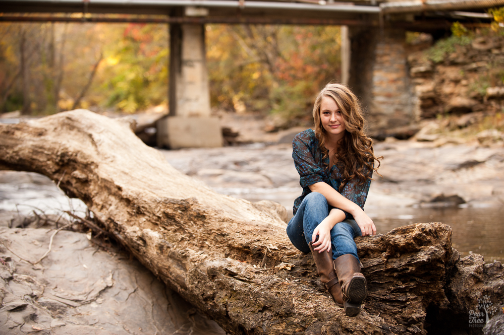 High school senior girl sitting on fallen tree at Sope Creek