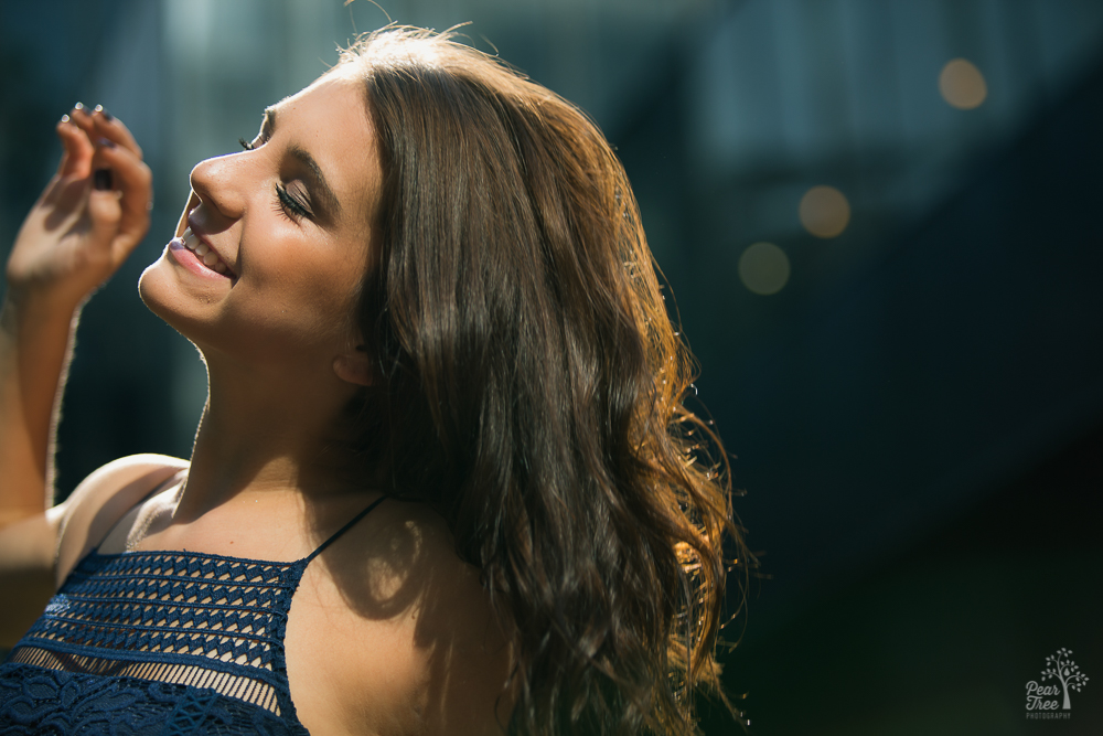 High school senior girl dancing and smiling in the sun