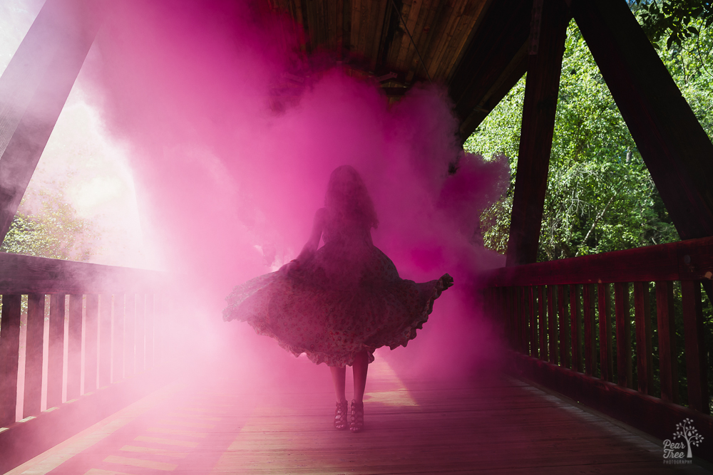 High school senior girl silhouetted on covered bridge in pink smoke