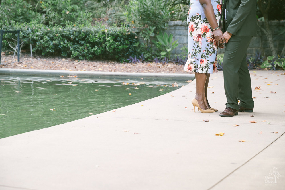 Two black women holding hands next to a pond.