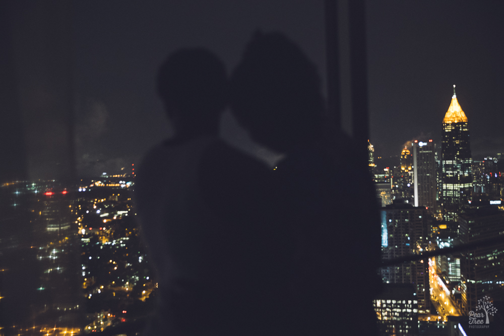 Two women embracing at night with Atlanta skyline in background.