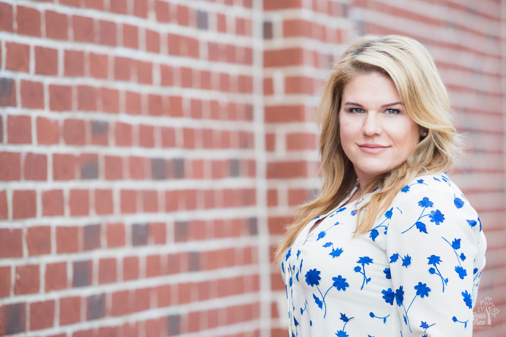 Blonde woman in white and blue blouse standing in front of red bricks in downtown Alpharetta