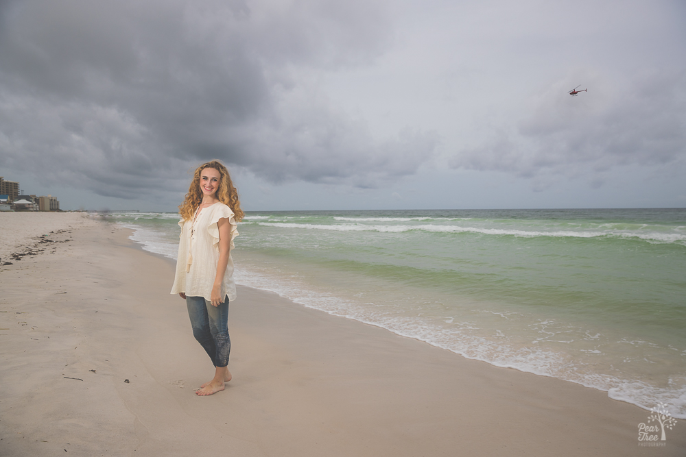 High school senior girl on beach with helicopter flying overhead