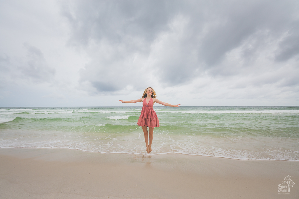 High school senior girl jumping waves in a pink dress