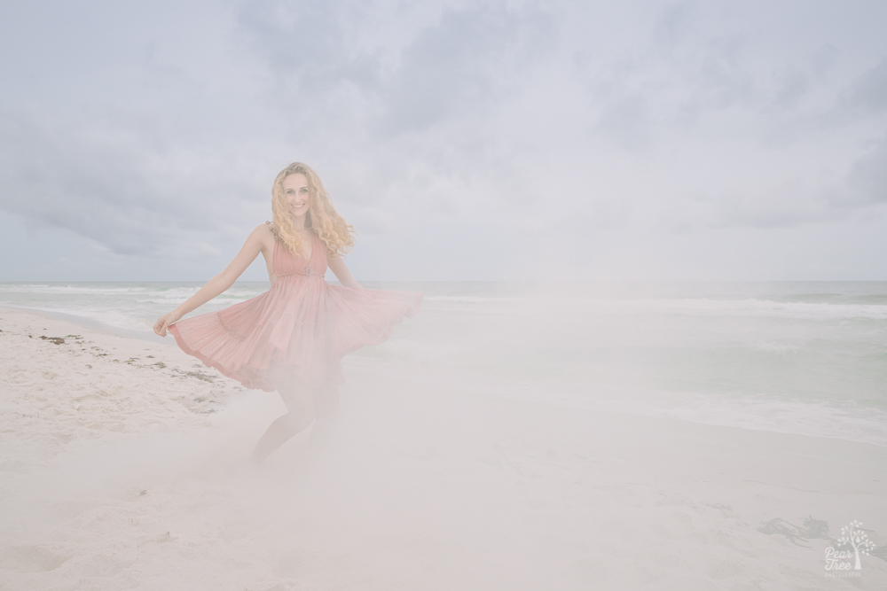 High school senior girl twirling on the beach in smoke