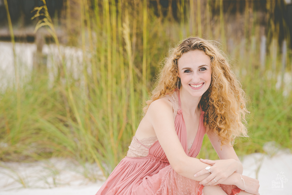 High school senior girl in pink dress sitting in front of tall beach grass