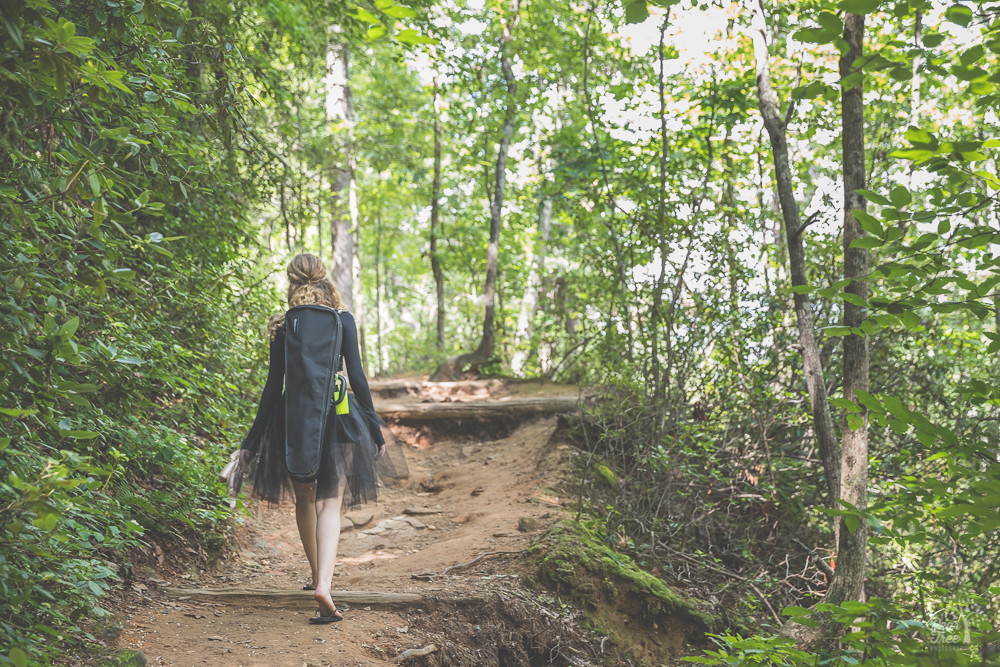 High school senior girl walking through woods with her violin and pointe shoes in hand