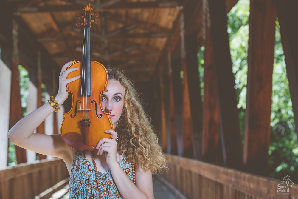 High school girl holding her violin in front of her face