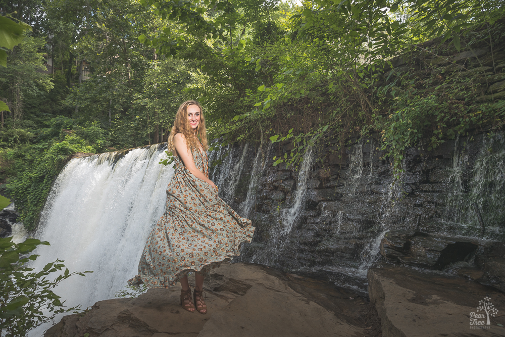 High school girl twirling her dress in front of Roswell Mill waterfall