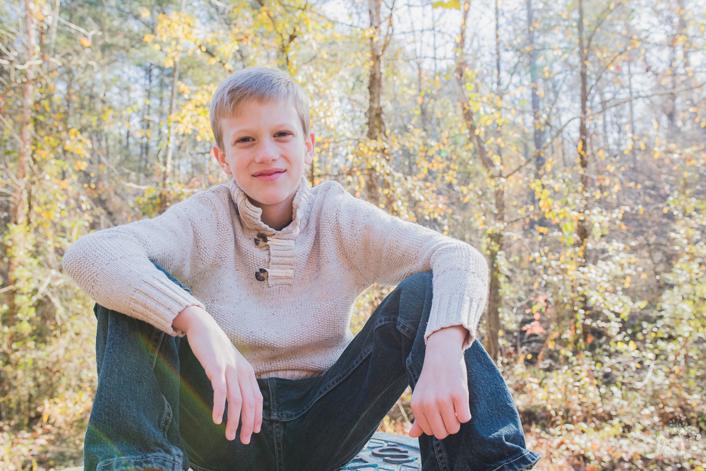 Pre-teen boy sitting in woods with elbows on knees