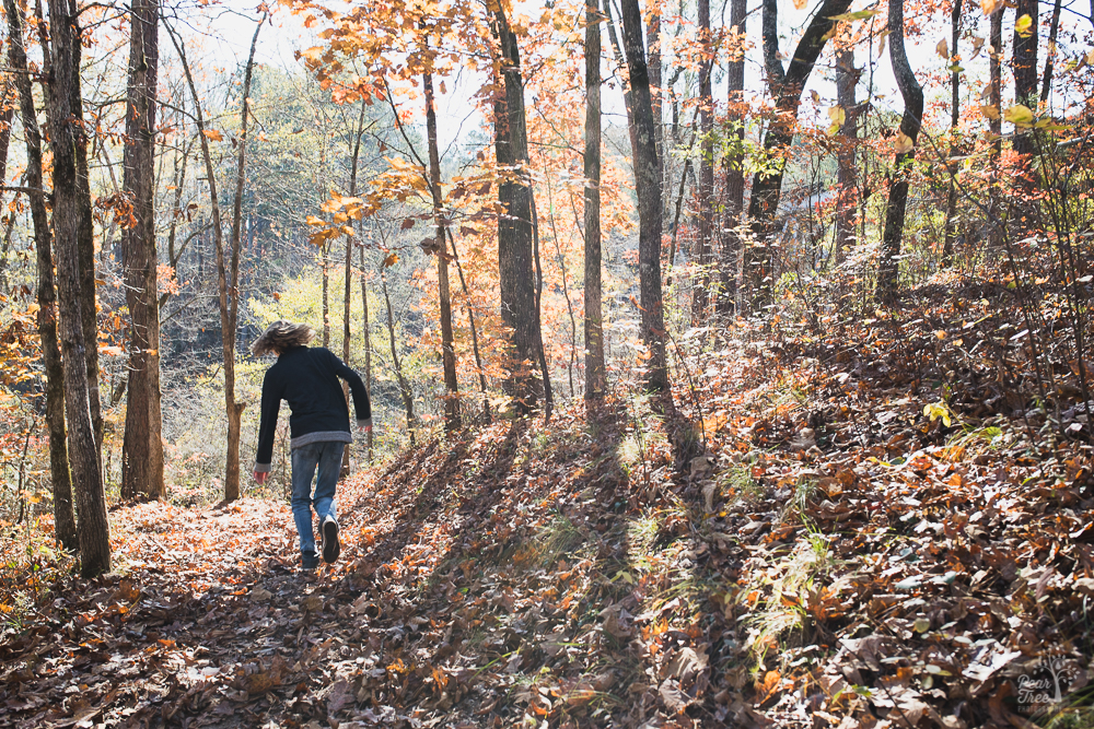 Teenage boy running off through fall leaves in the woods