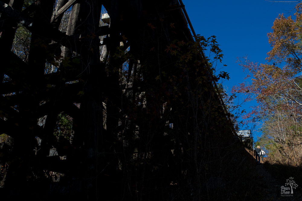 Two boys climbing trail up next to trestle into blue sky