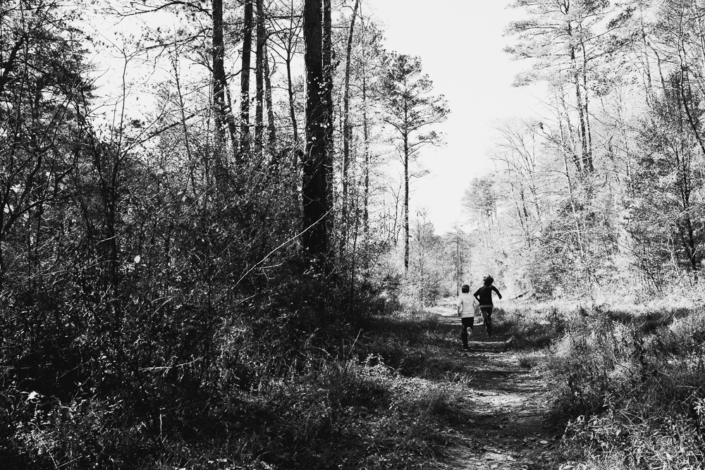 Two boys running off on a trail in the woods