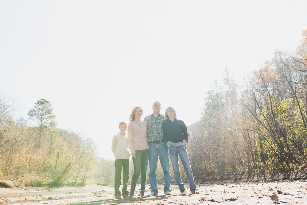 Family of four standing together in dry creek bed with sun shining down