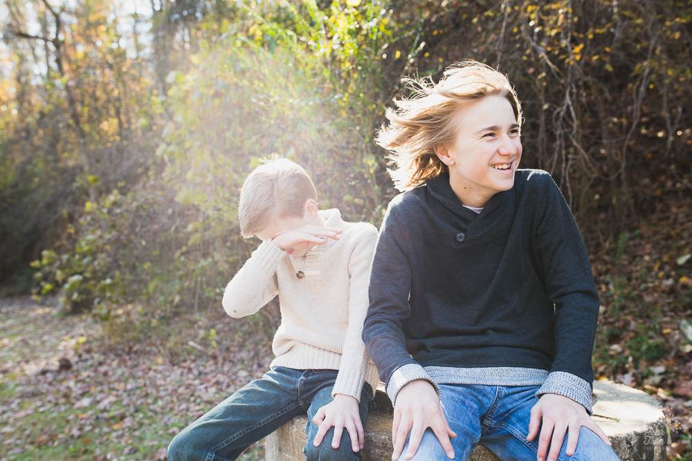 Two boys sitting in woods with wind blowing their hair