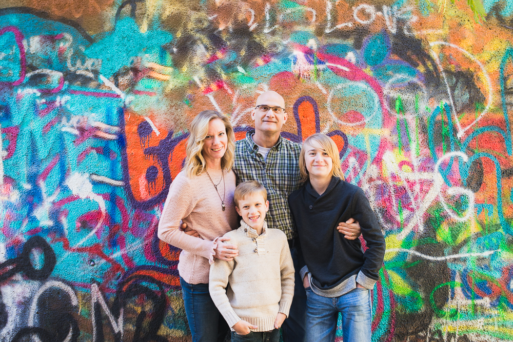 Family of four with two boys standing in front of graffiti wall