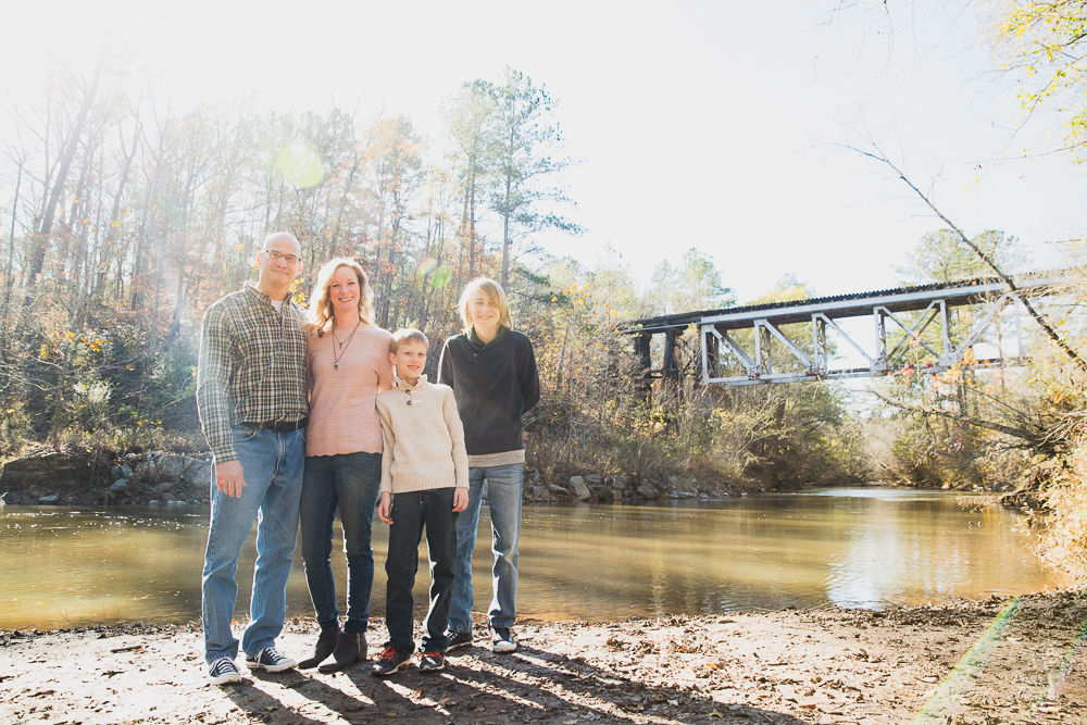 A family of four standing in the sunshine along a creek with a train trestle in the background