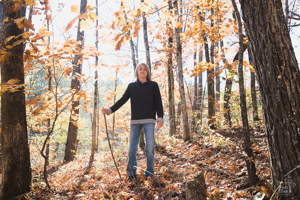 A teenage boy standing with a walking stick in the woods with fall leaves