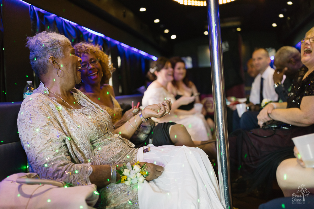 Groom's mom and aunt celebrating on party bus with wedding party
