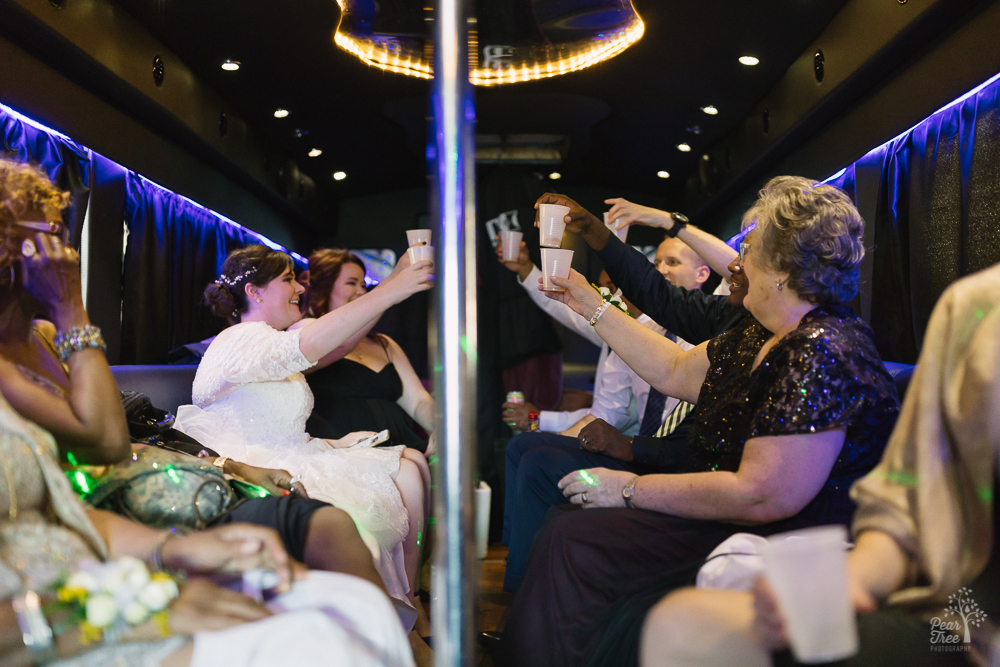 Bride and groom toasting on party bus with wedding party
