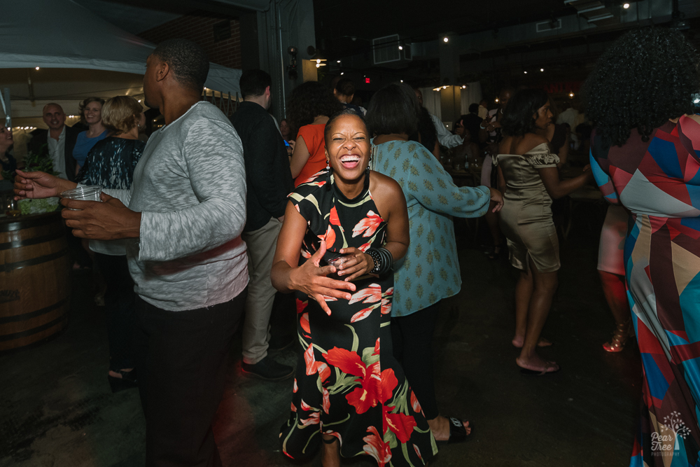 Woman laughing hard while dancing at Urban Tree Cidery wedding reception