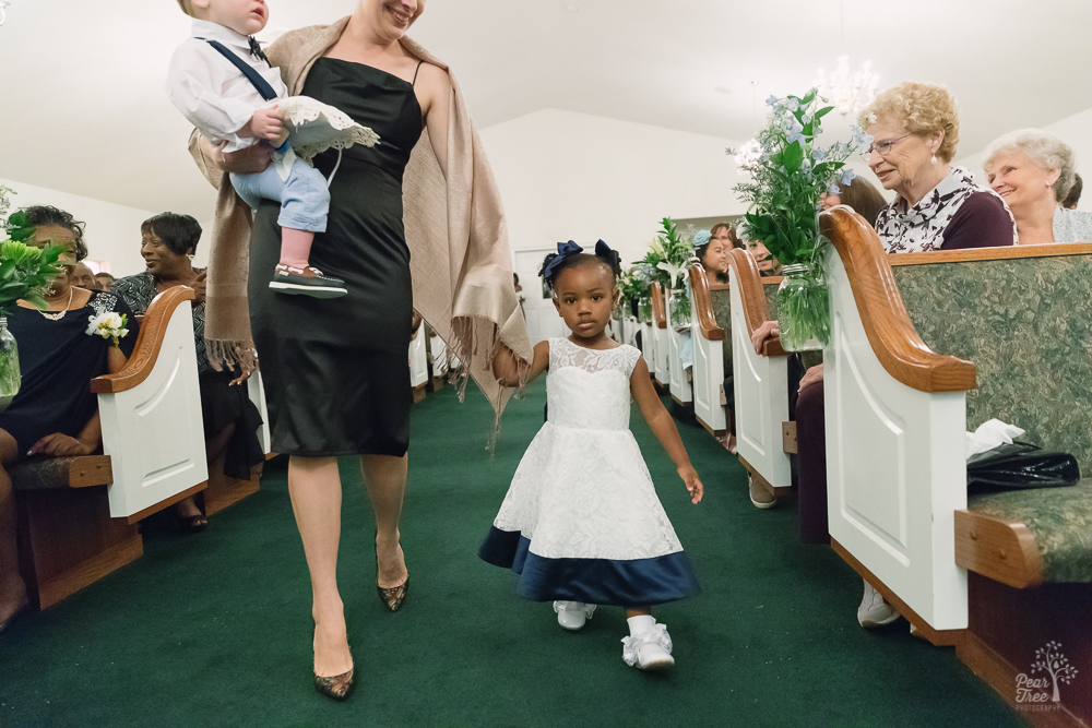 Flower girl walking and ring bearer being carried down church aisle