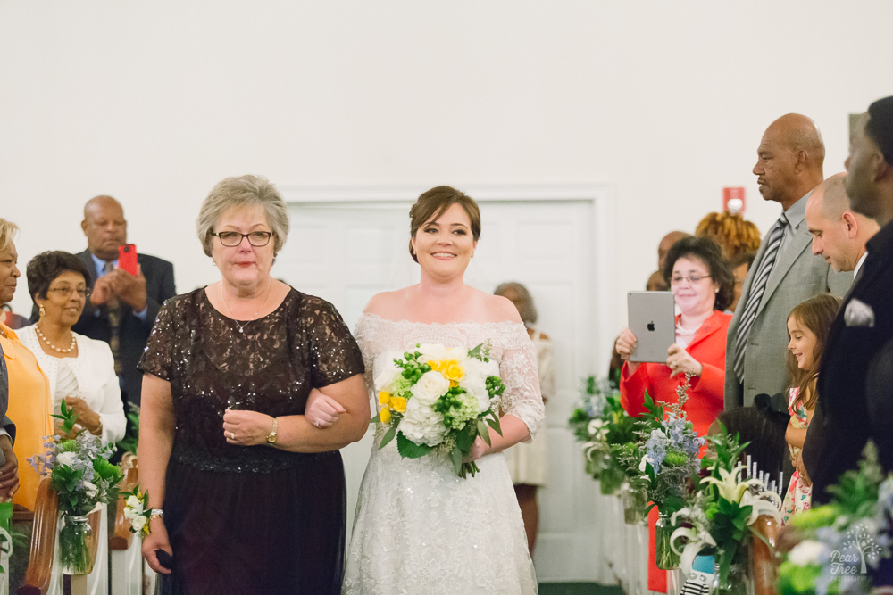Bride being escorted down wedding aisle by her emotional mom