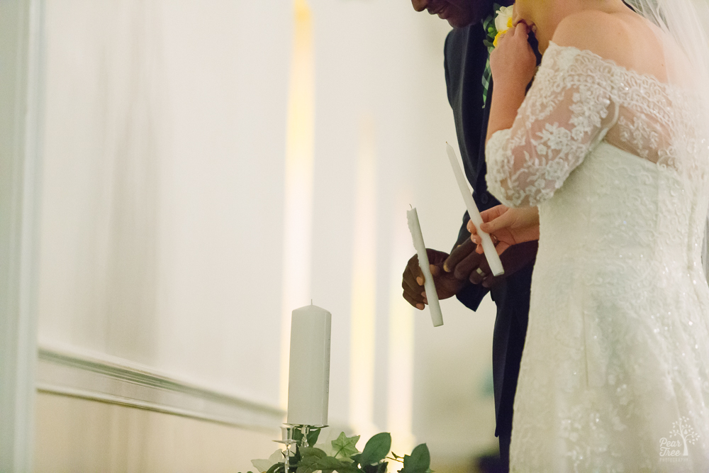 Bride and groom lighting the unity candle after blowing out their flames